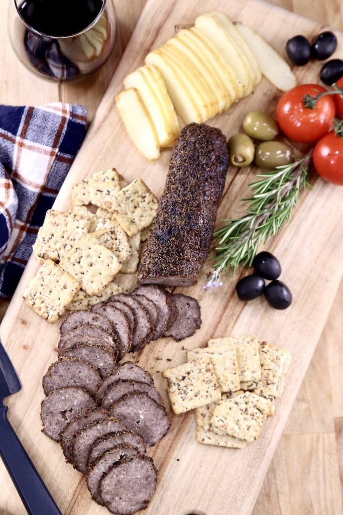 Venison Pepperoni charcuterie board with cheese, crackers, olives, rosemary and tomatoes