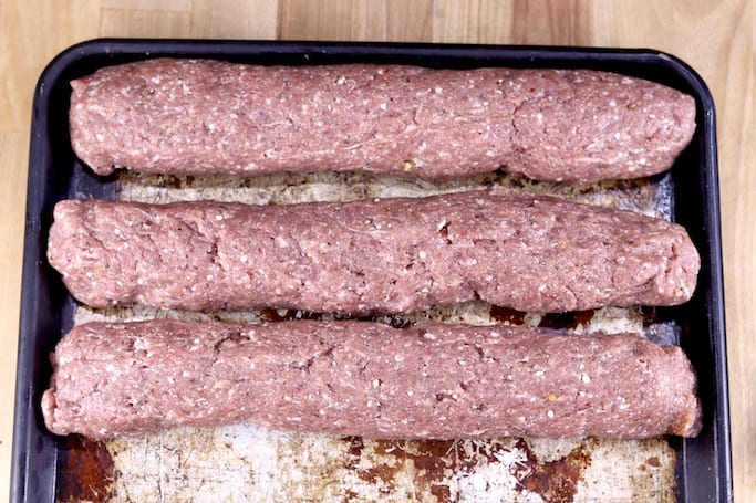 Rolls of uncooked summer sausage - 3 on a sheet pan