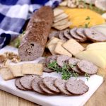 Venison summer sausage sliced on a baord, with cheese, crackers, herbs and nuts