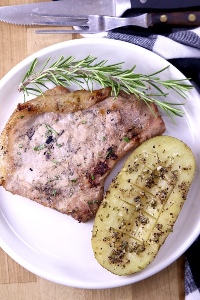 Plate with grilled pork chop and half of a potato with rosemary