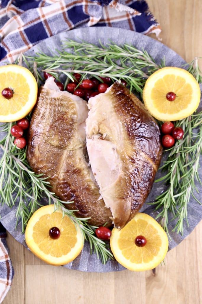 2 turkey breasts - smoked, on a platter with orange slices, cranberries and fresh rosemary - overhead view