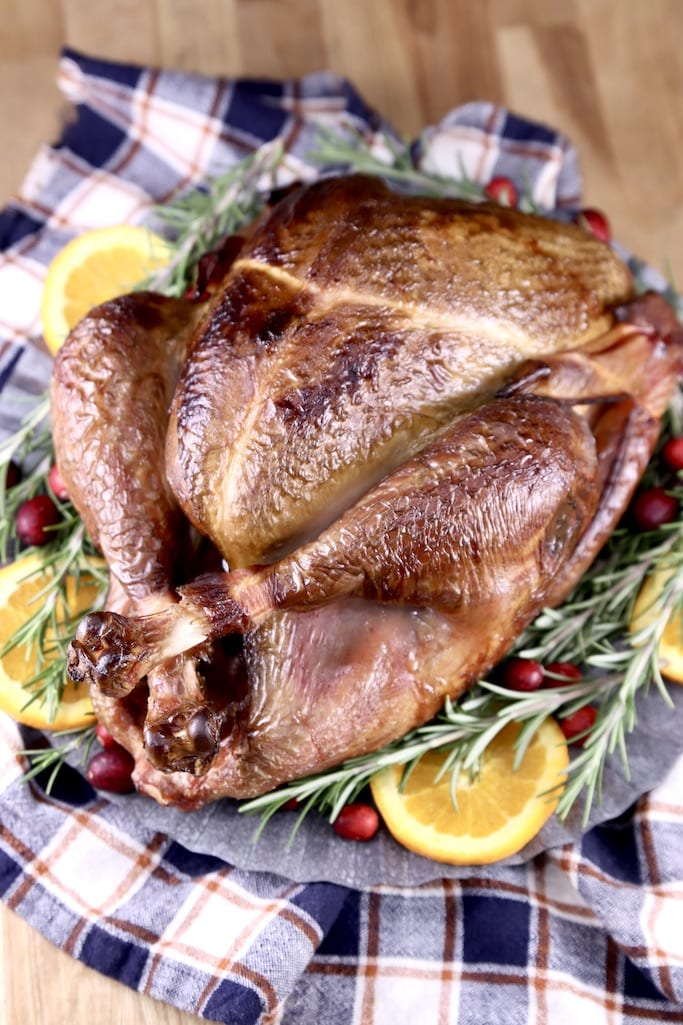 Smoked Apple Cider Marinated Turkey on a platter with orange slices, rosemary and cranberries