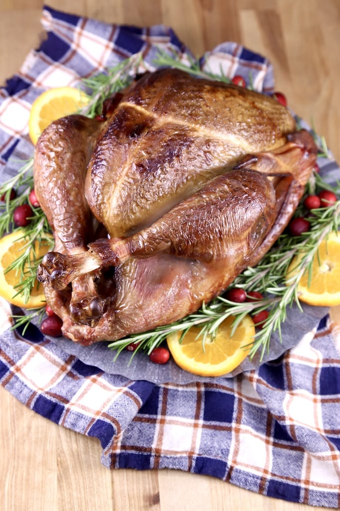 Apple Cider Smoked turkey on a platter with plaid napkin, garnish of orange slices, fresh cranberries and rosemary