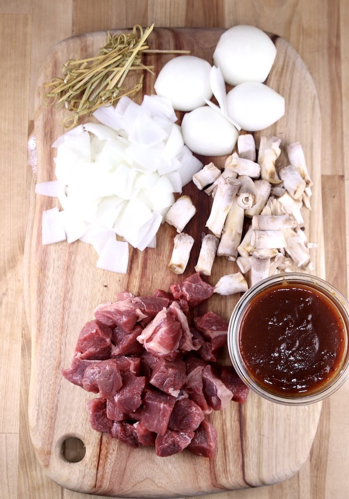Ingredients for steak bites, sirloin steak, onions, mushroom stems, bbq sauce and bamboo picks on a cutting board