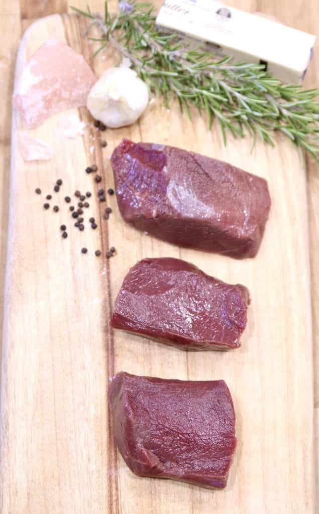 Venison tenderloin steaks on a cutting board - raw with butter, pepper, garlic, chunk of pink salt, fresh rosemary and garlic