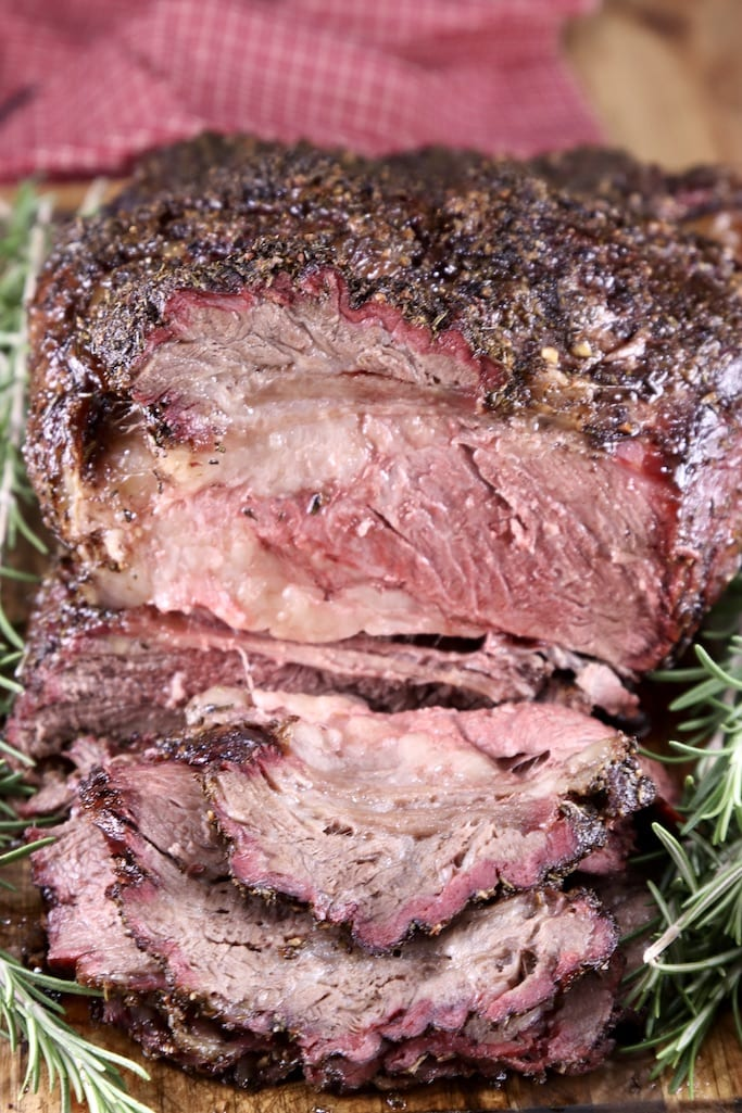 Sliced prime rib roast on a cutting board, close up view