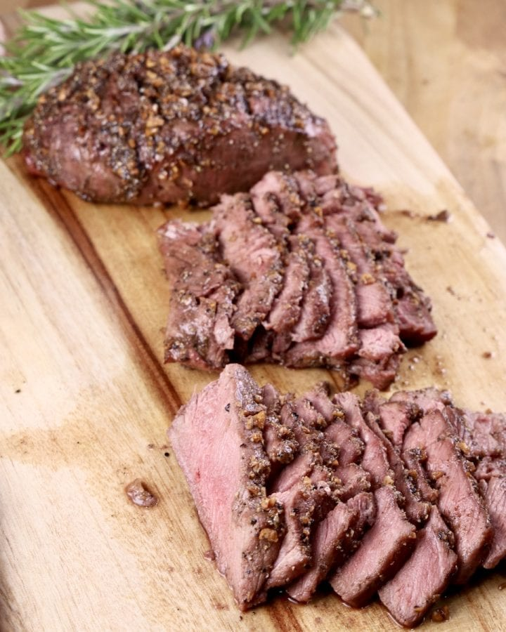 Grilled Venison steaks, one whole, 2 sliced on a cutting board with rosemary sprig