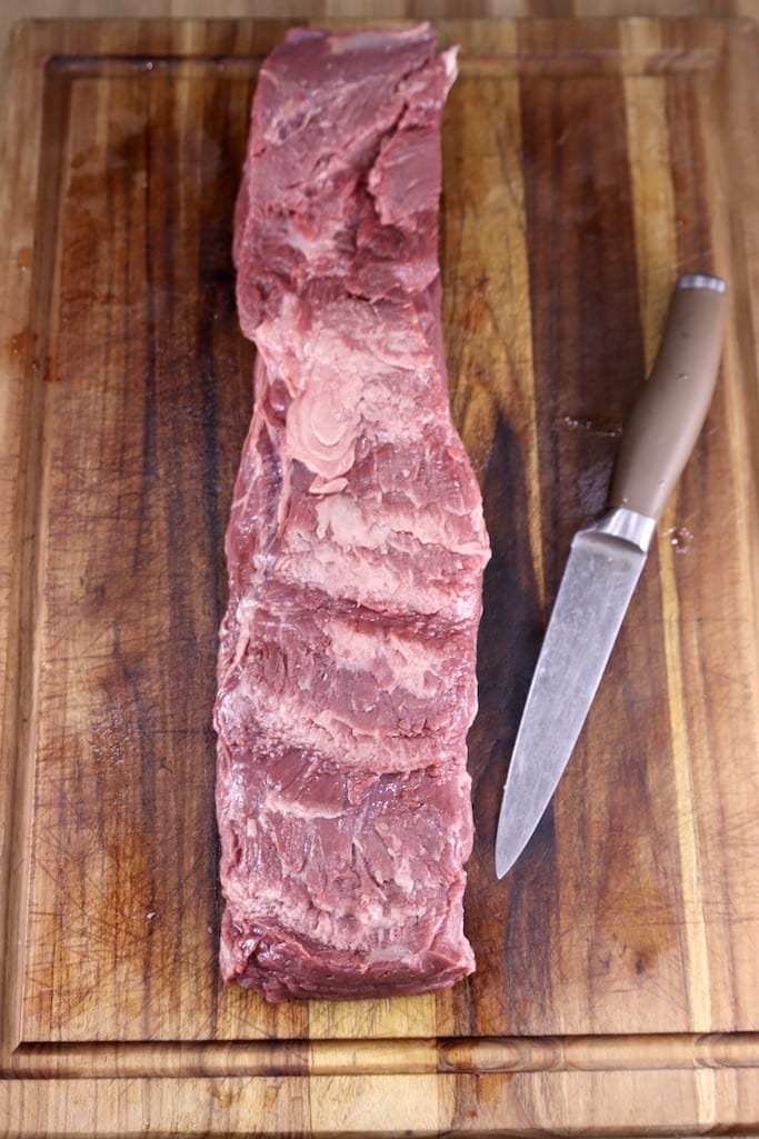trimmed beef tenderloin with a knife on a cutting board