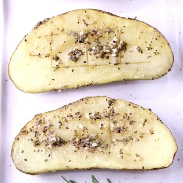 Garlic Butter Baked Potatoes with herbs, 2 halves on a white plate