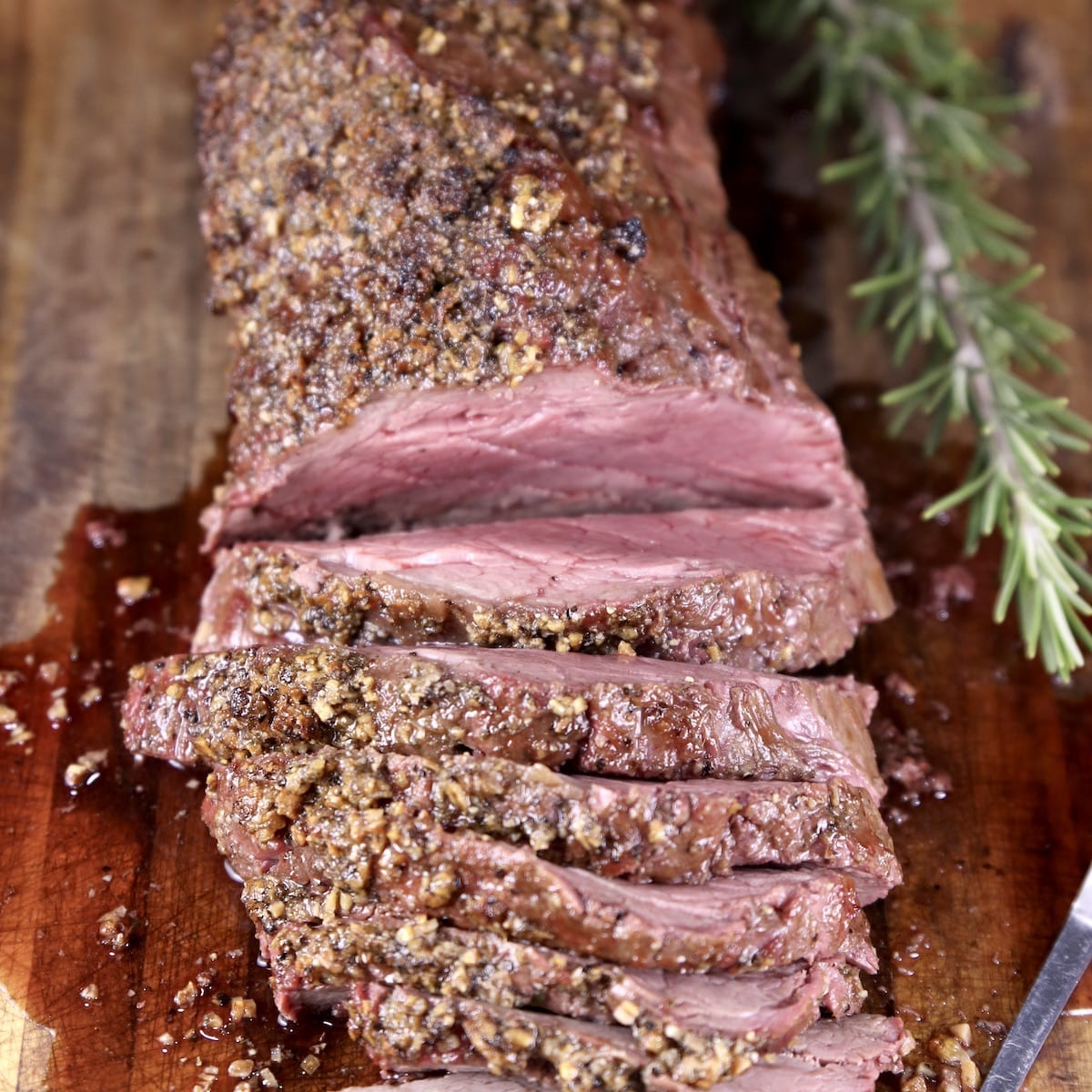 Grilled Garlic Butter beef Tenderloin partially sliced on a cutting board with rosemary sprig