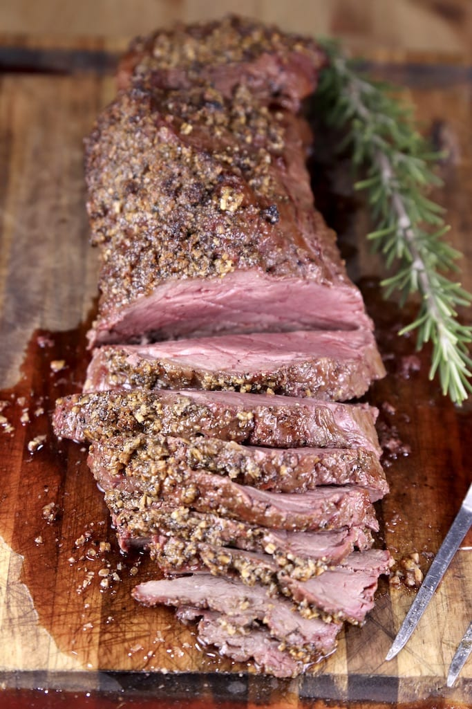 Partially sliced beef tenderloin roast on a cutting board with rosemary sprig