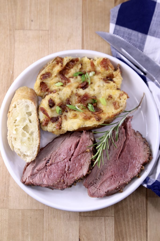 Plate with twice baked potato, slice of baguette and 2 slices of beef tenderloin