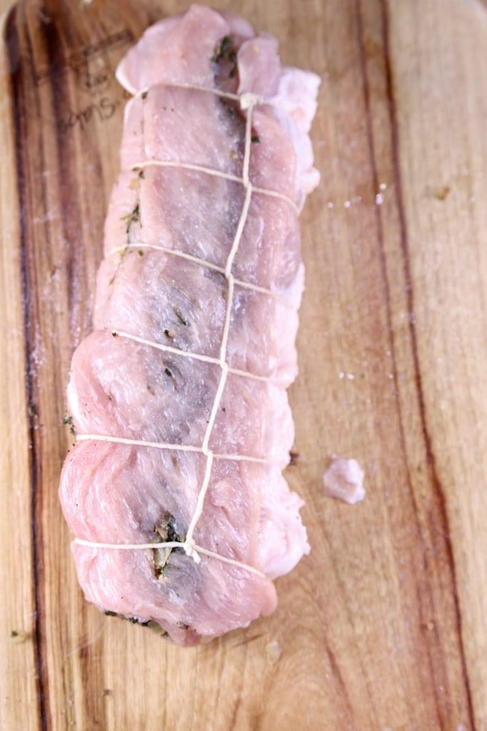 Butcher twine tied pork tenderloin on a cutting board