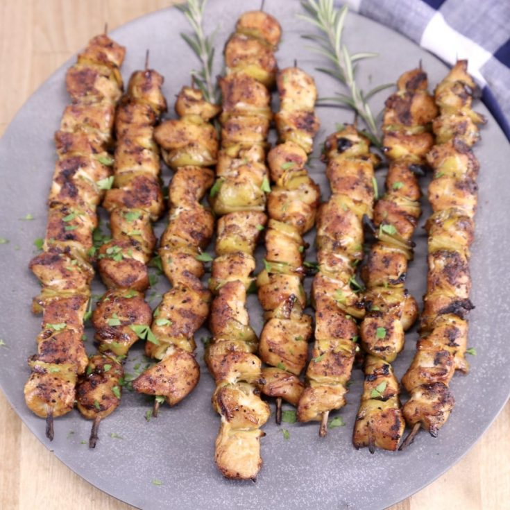 grilled Chicken skewers on a gray round platter