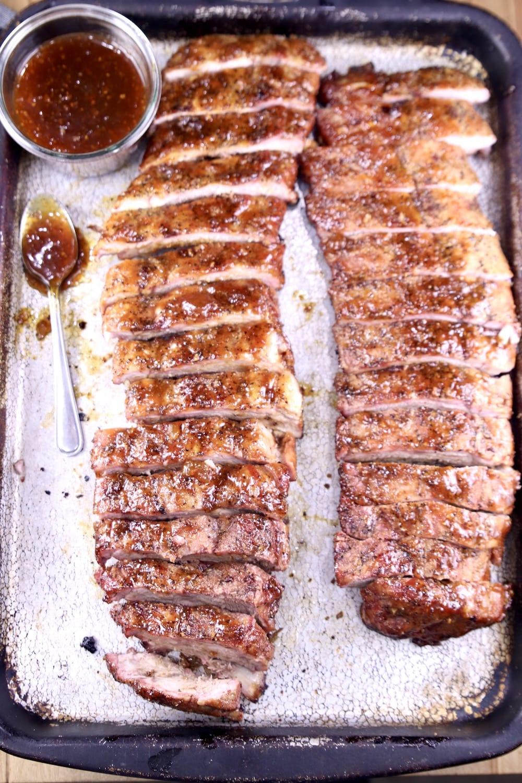 BBQ sauce and 2 racks of ribs sliced