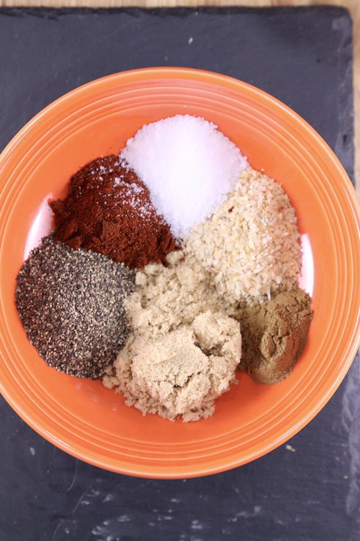Seasonings and brown sugar for gumbo in an orange bowl