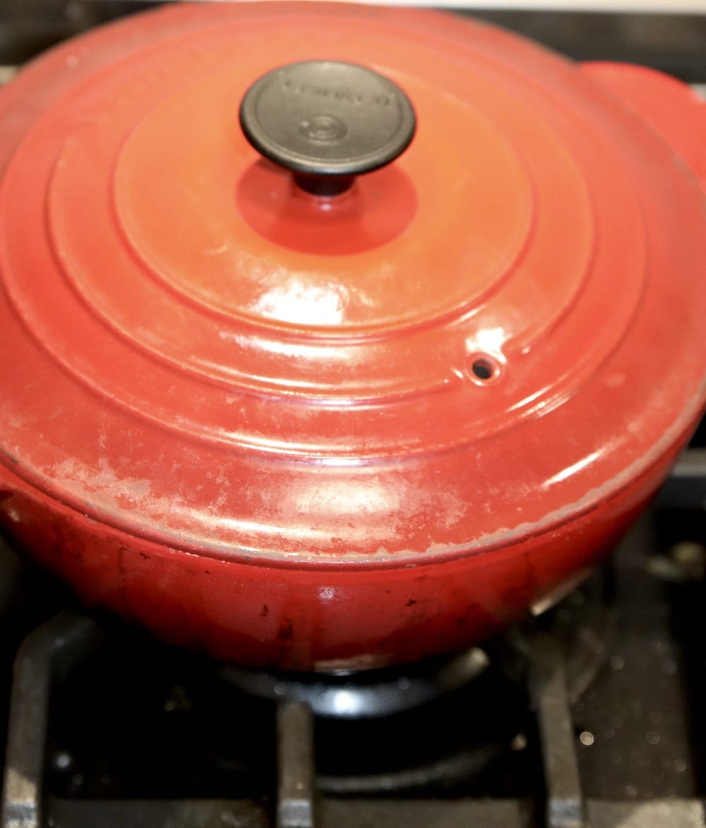 Red saucepan with lid on stove