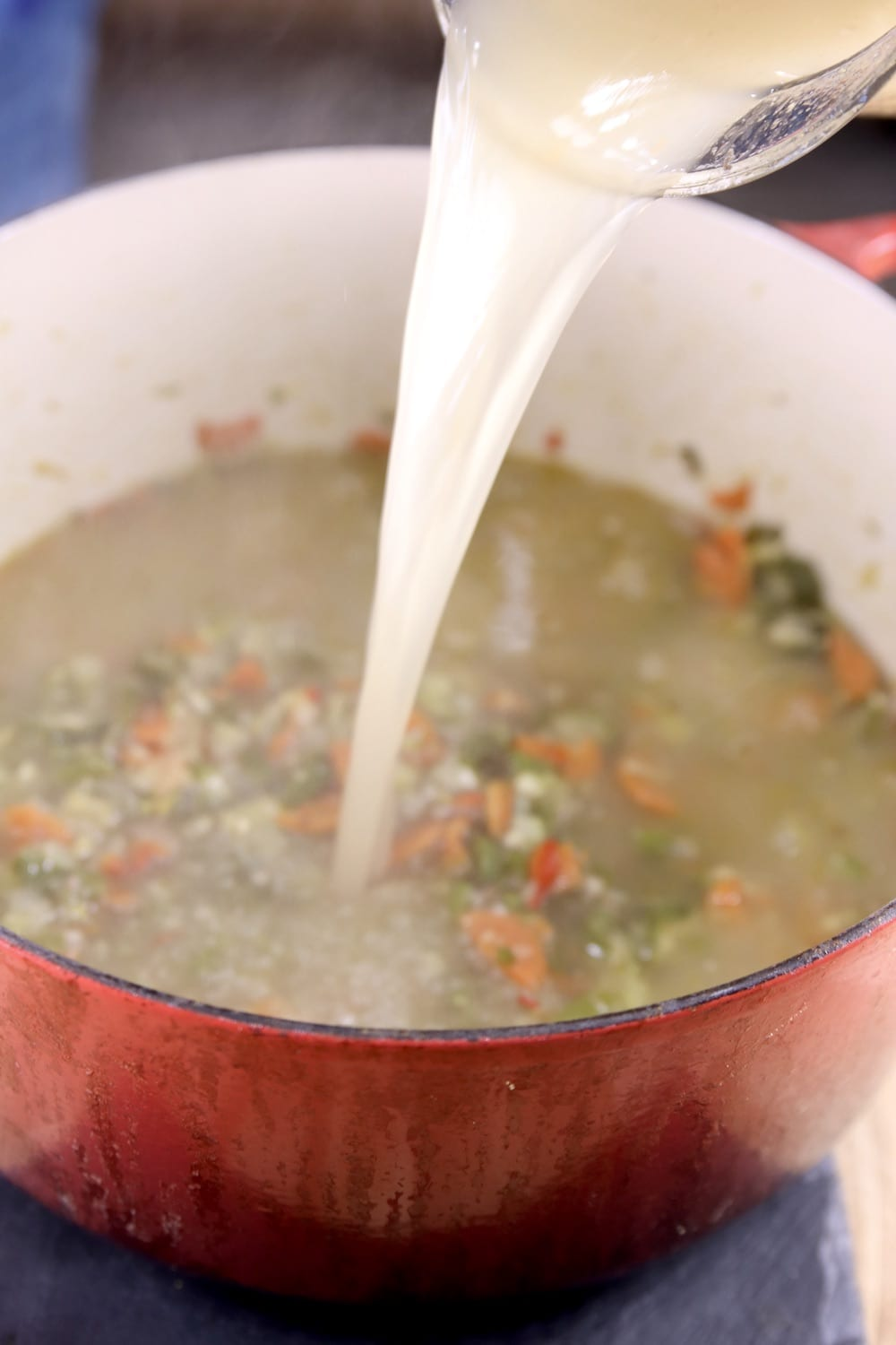 Soup pan with vegetables, pouring in chicken broth