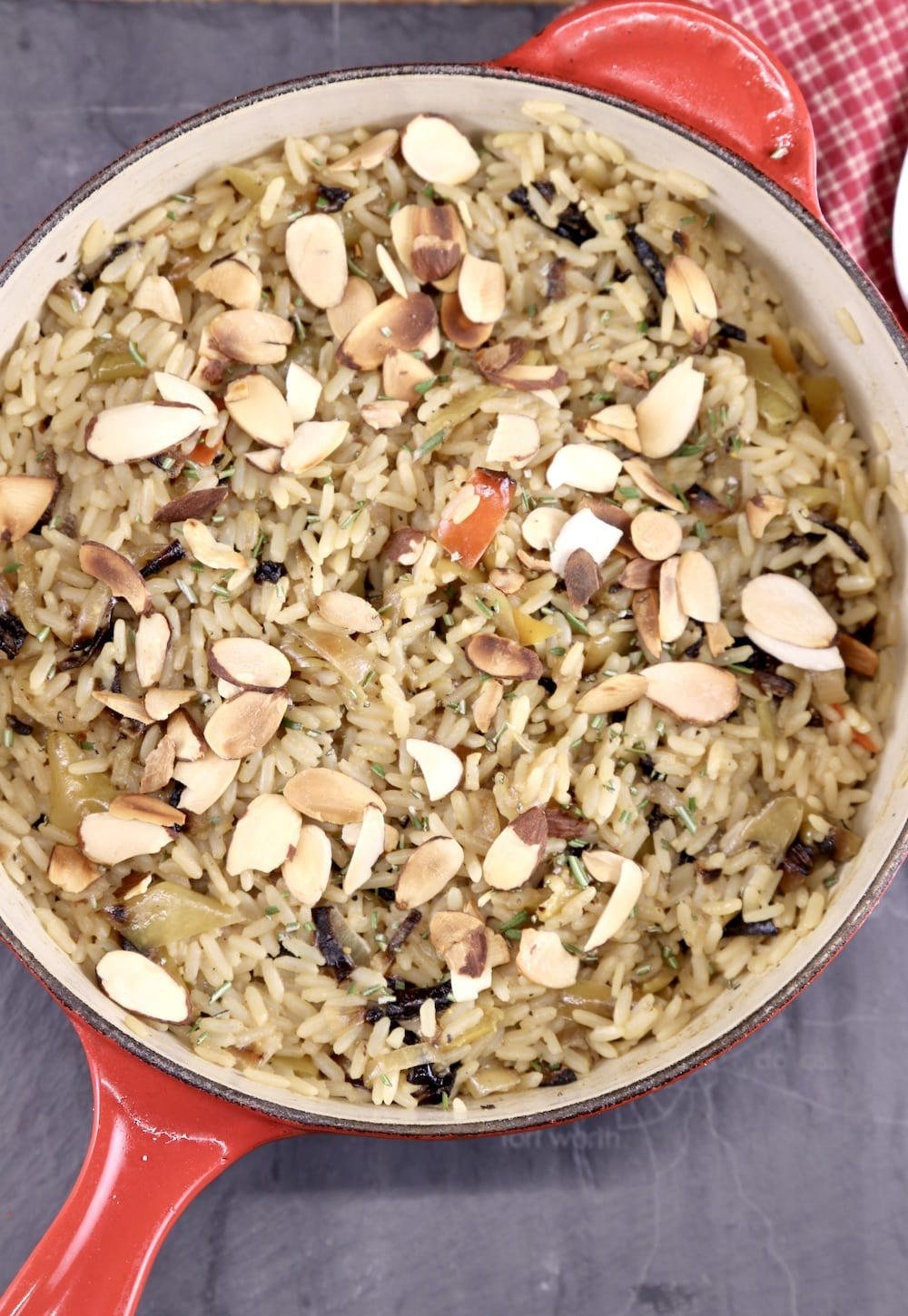 Toasted almonds over rice pilaf in red pan