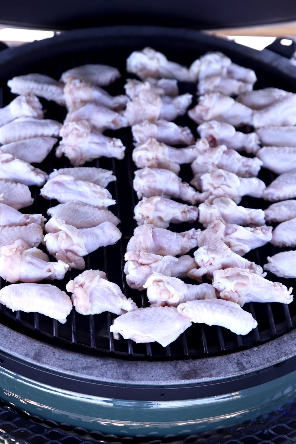 big green egg grill with chicken wings on the grate
