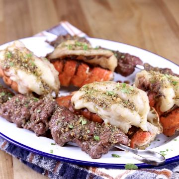 Garlic Butter Lobster Tails on a platter with steak bites