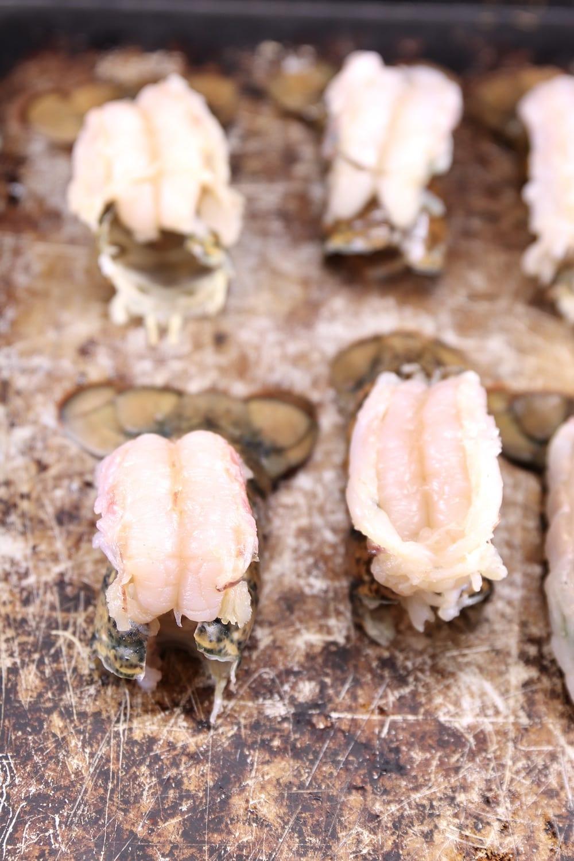 Butterflied lobster tails on a baking sheet