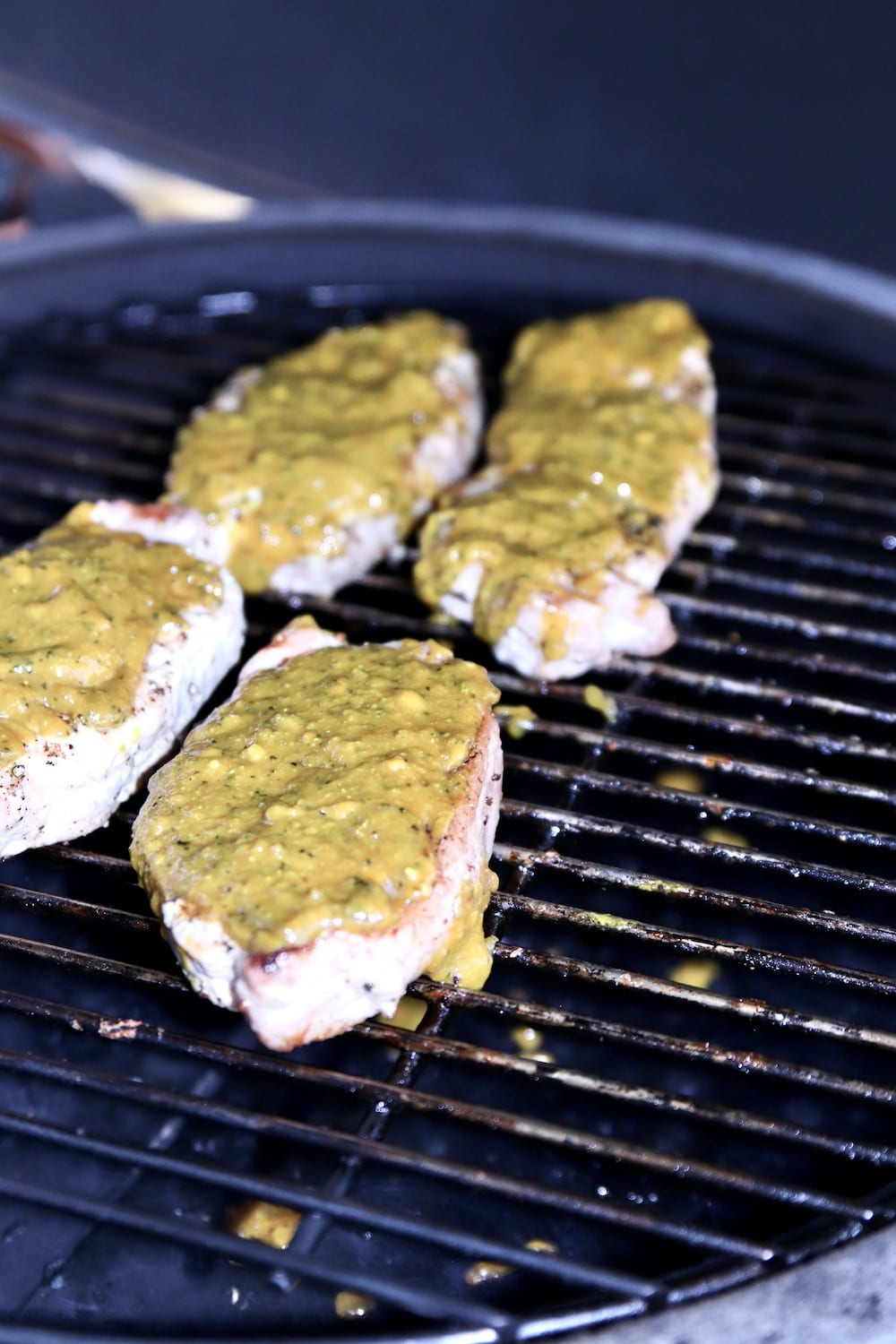 4 pork chops on a grill with mustard bbq sauce