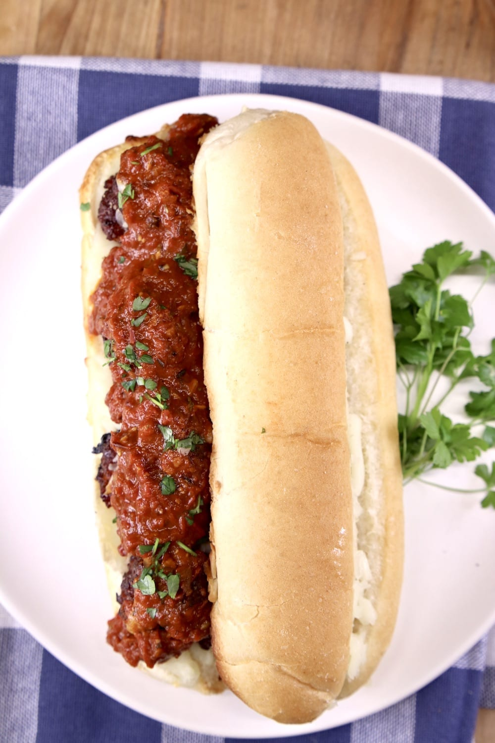 Meatball Sub sandwich on a white plate with parsley garnish