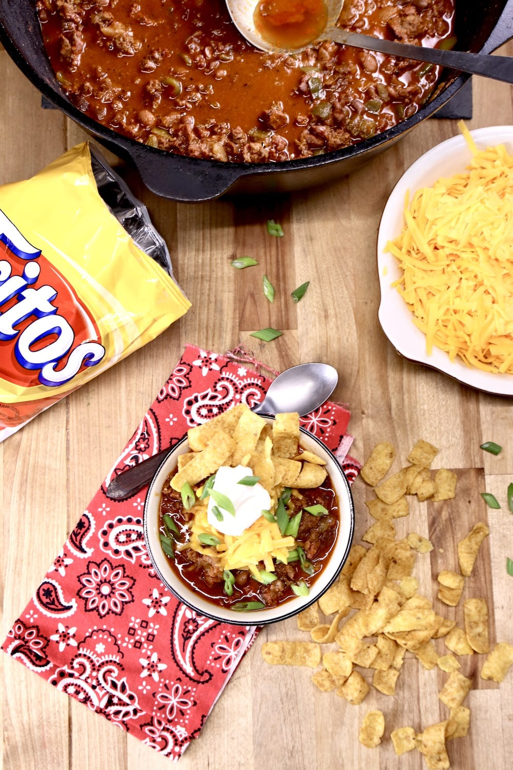 Smoked Chili: dutch oven, bowl topped with cheese, sour cream, Fritos, bag of Fritos, cheese in a bowl