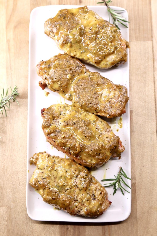 platter of 4 rosemary mustard pork chops with rosemary garnish