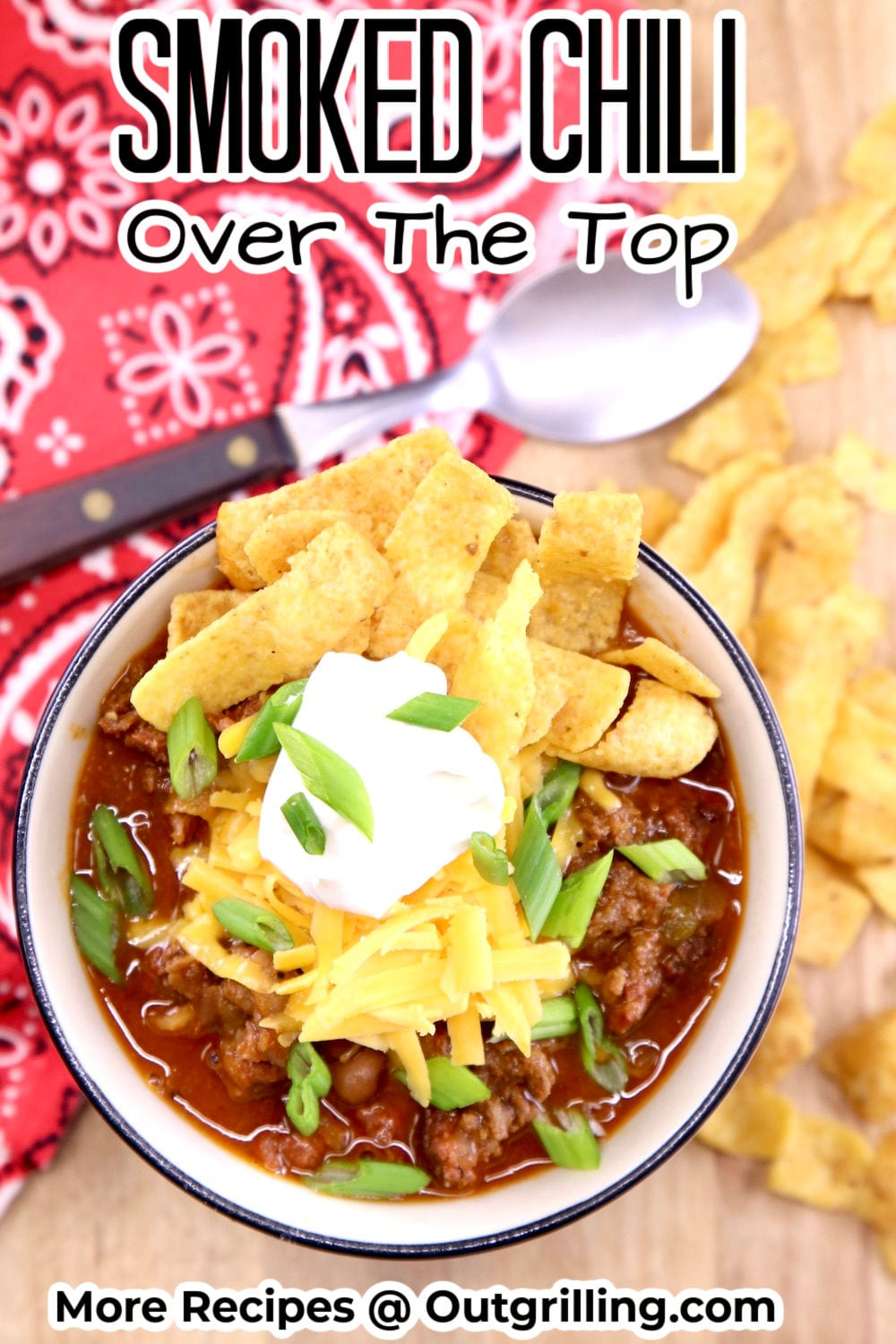 Bowl of chili topped with cheese, sour cream, green onions and Fritos, spoon and bandana napkin to the side