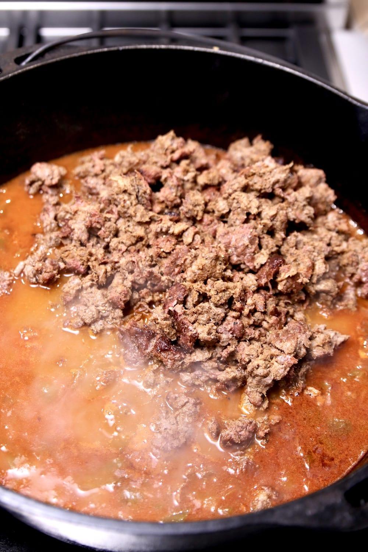 Adding smoked chili meat to cast iron dutch oven of chili