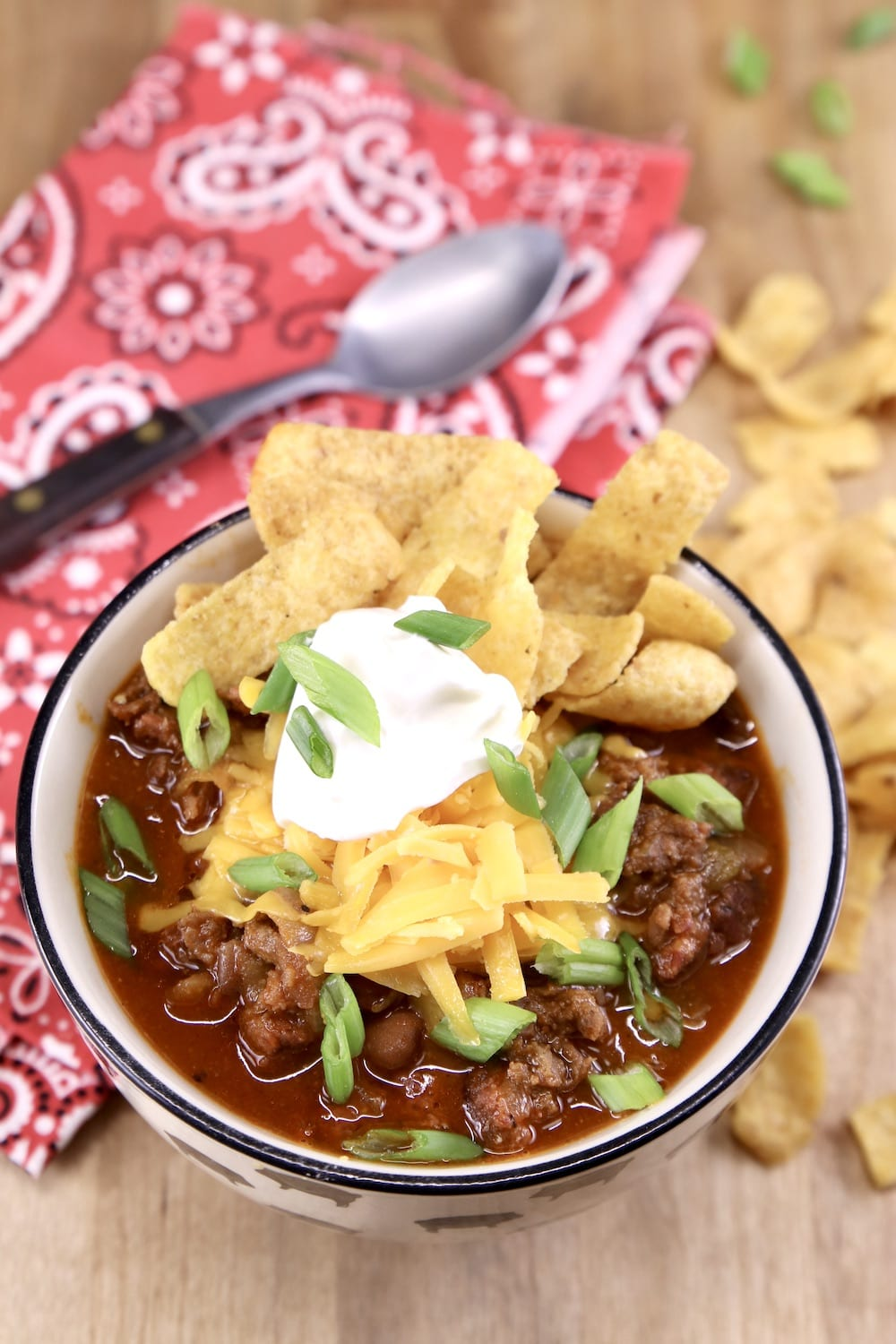 Bowl of chili with sour cream, cheese and fritos