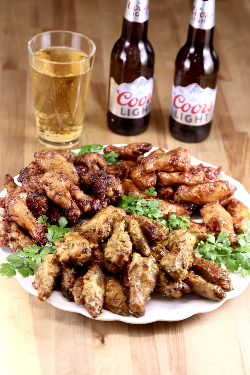 Platter of chicken wings with Coors beer bottles and one glass
