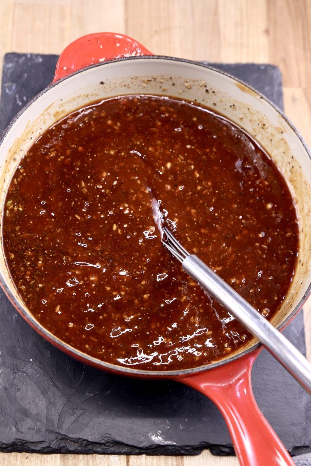 Pan of bbq sauce with a whisk