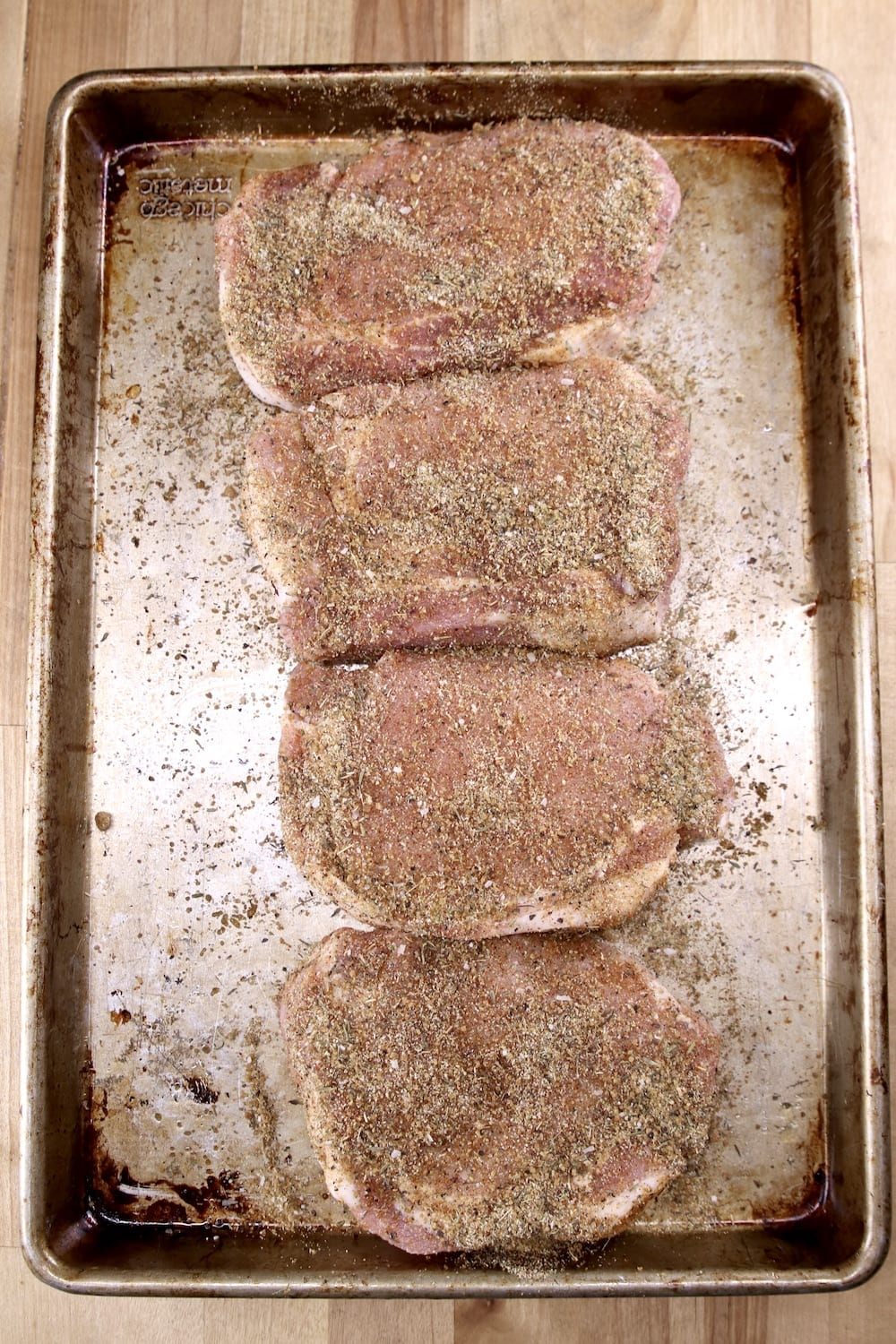 sheet pan with 4 dry rubbed pork chops