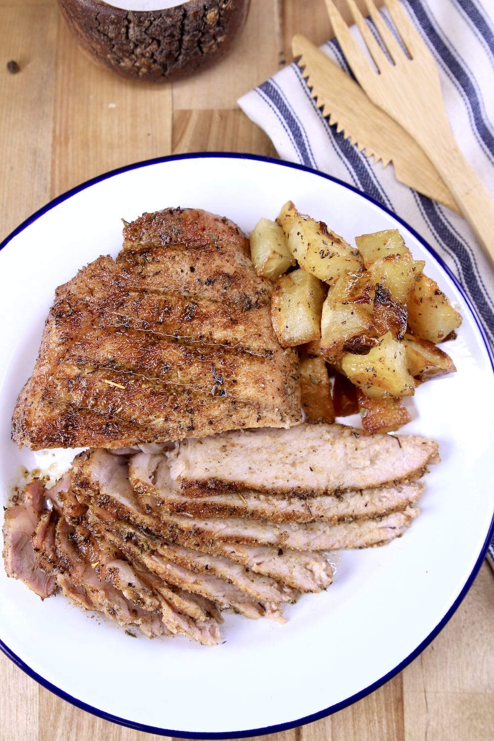 Grilled pork chop, partially sliced on a plate with roasted potatoes