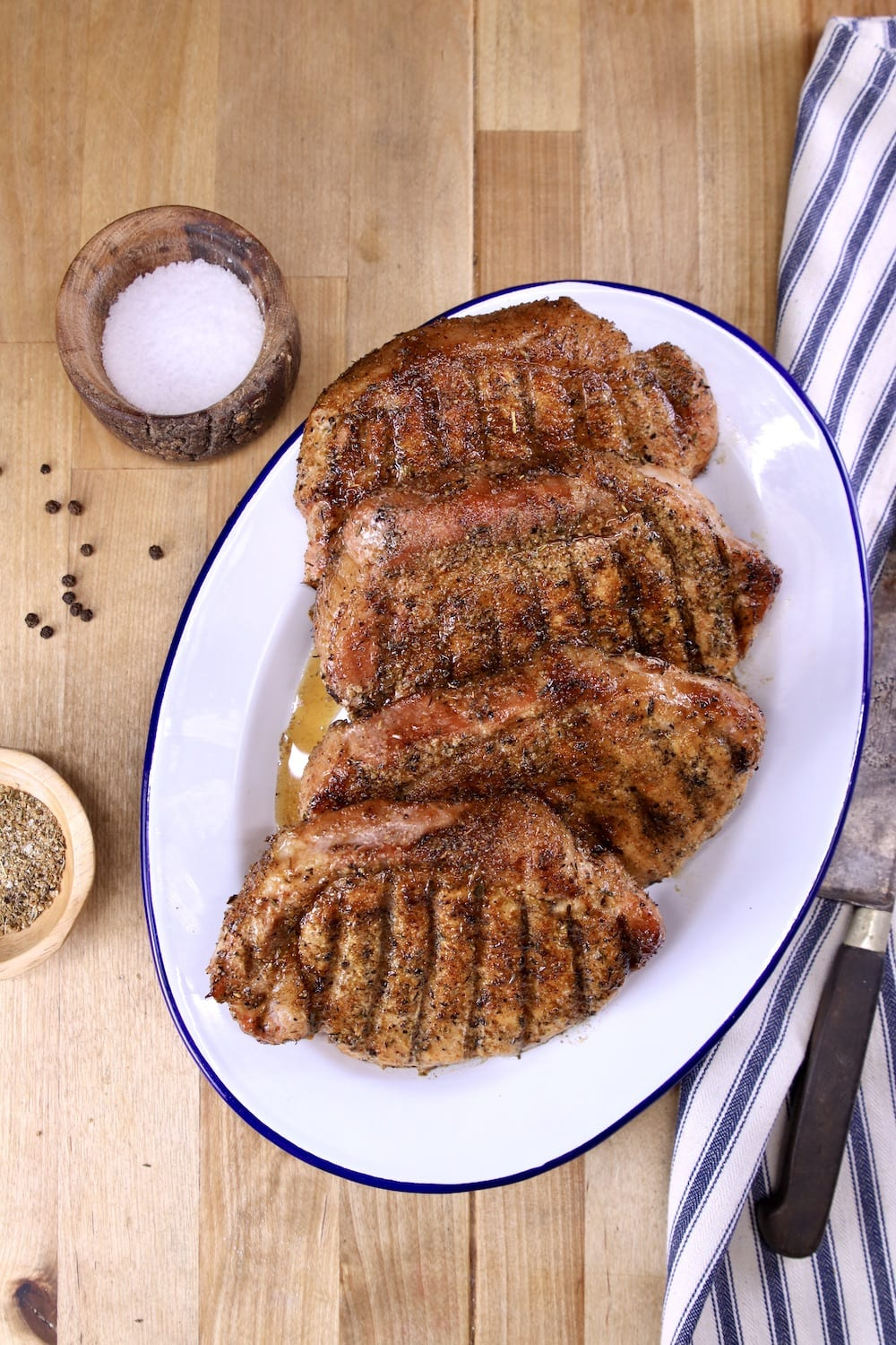 Grilled Pork Chops resting on a platter with bowl of salt