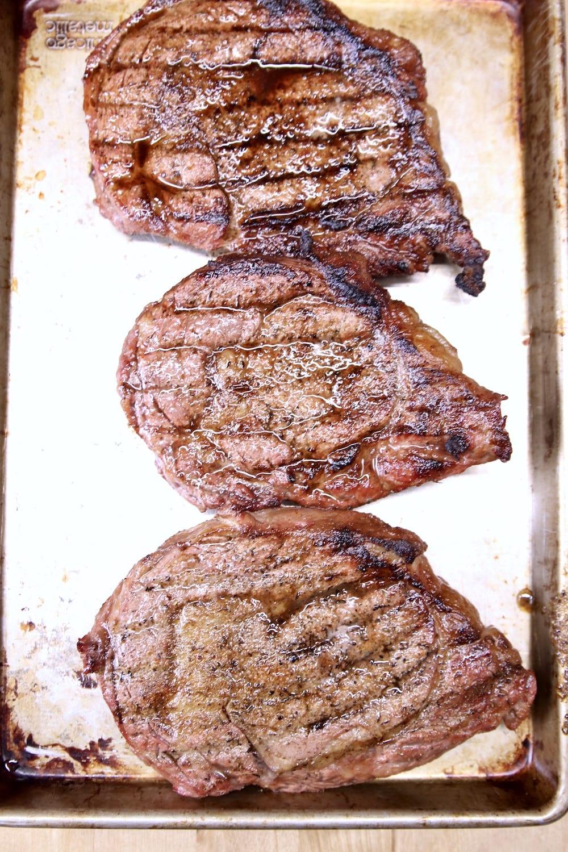 3 grilled ribeye steaks on a sheet pan