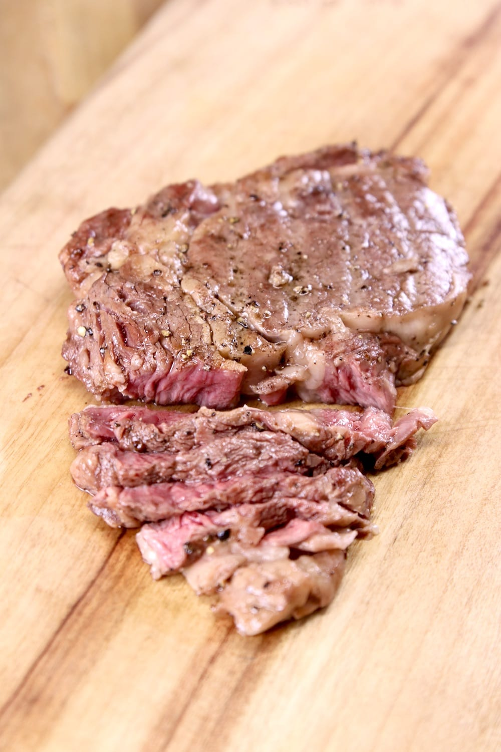 Grilled ribeye steak partially sliced on a cutting board