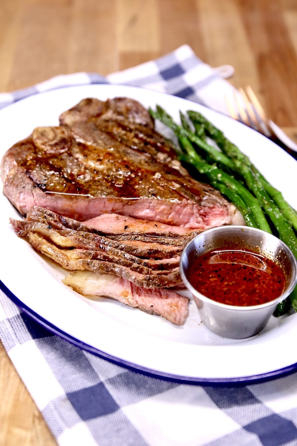 Grilled T Bone Steak partially sliced with cup of steak sauce and asparagus