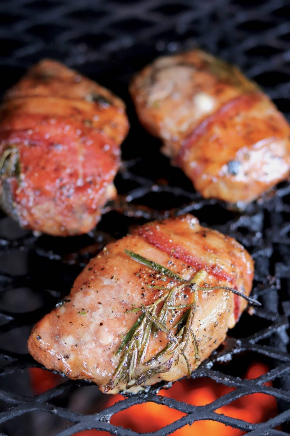 Pork chops on a grill with rosemary and bacon