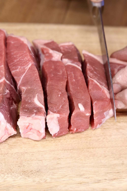 Slicing sirloin roast on a cutting board for stew