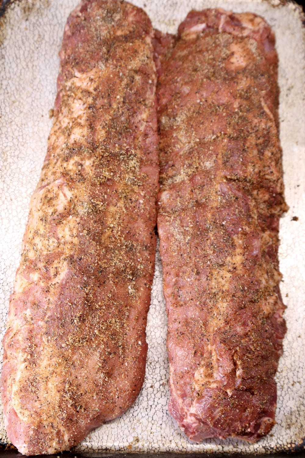 2 racks of ribs on a sheet pan with dry rub for grilling