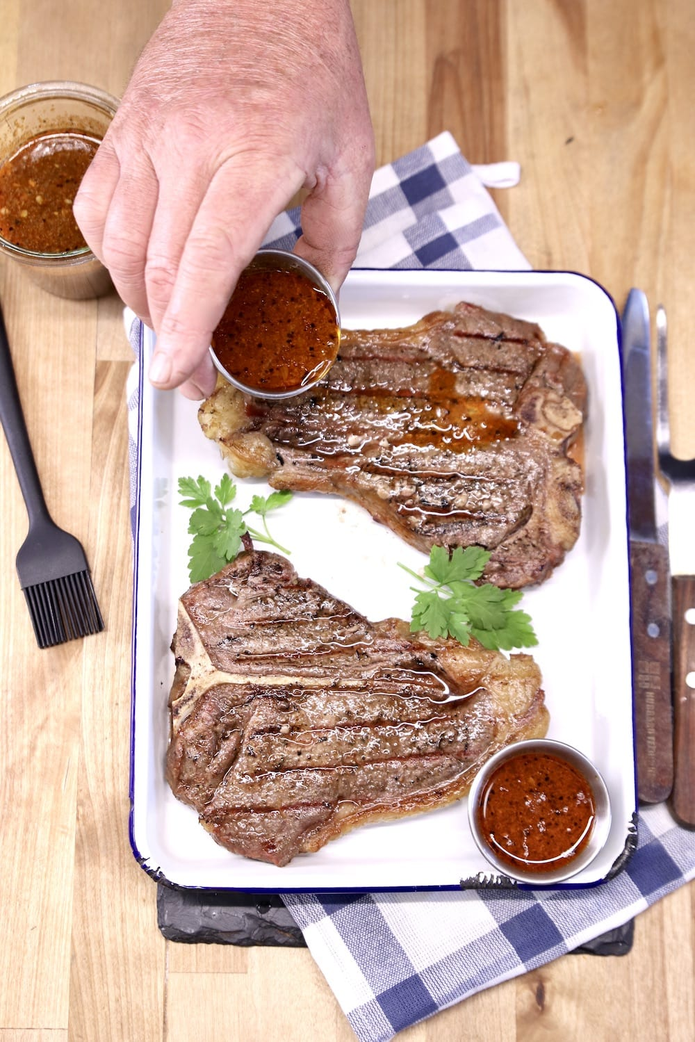 Drizzling sauce over grilled T-Bone Steaks - 2 on a platter