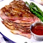 Whiskey Steak Sauce with T-Bone Steak on a plate with asparagus