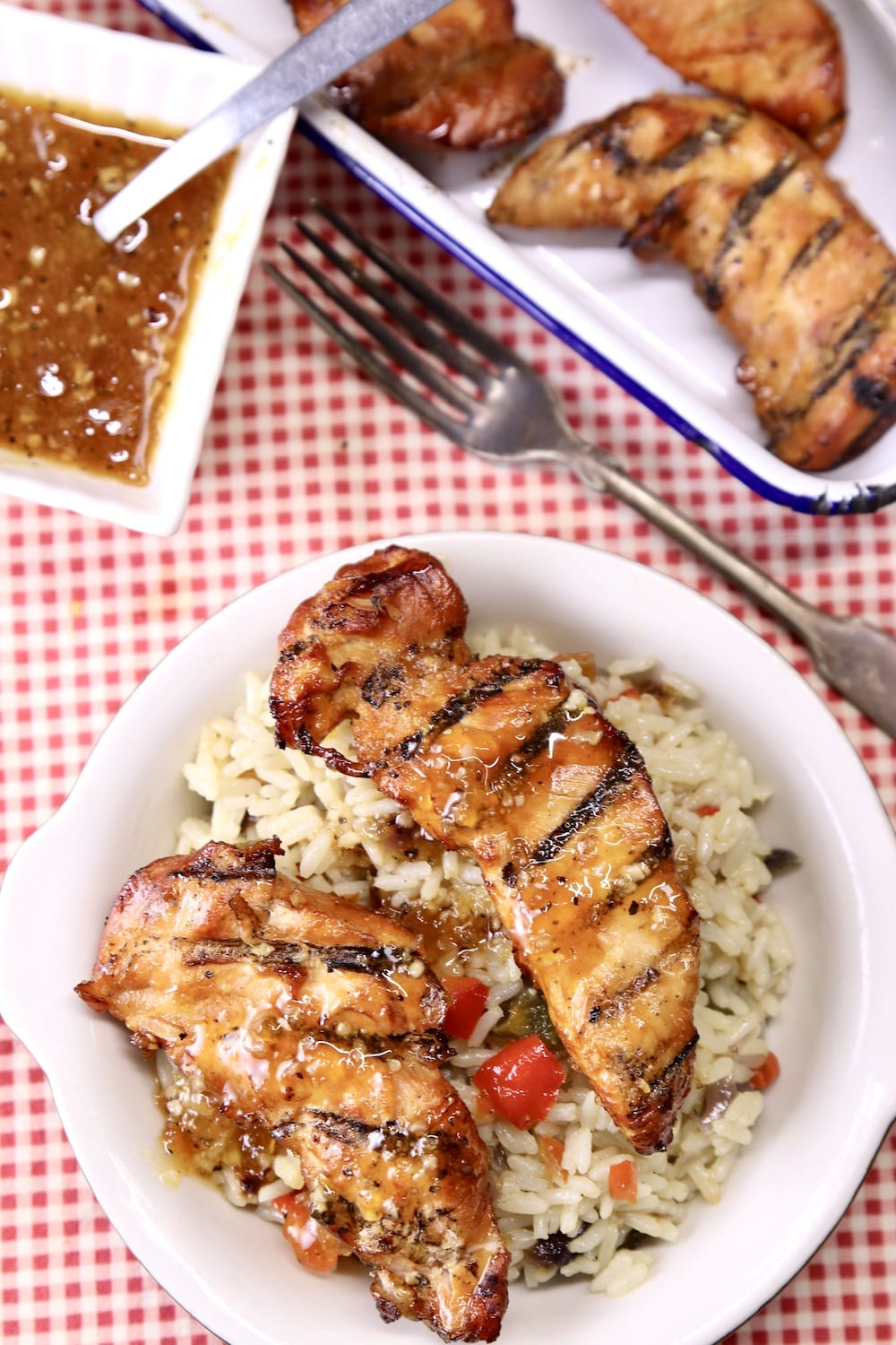 chicken tenders with rice pilaf on a plate, platter of tenders, bowl of sauce