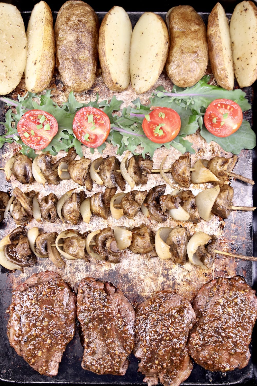 sheet pan with grilled steaks, potatoes, mushrooms on skewers, lettuce and tomato