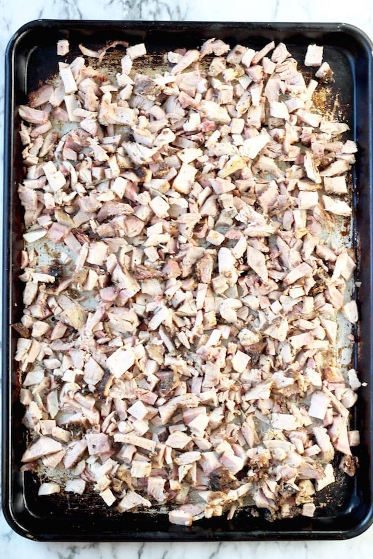 chopped pork for carnitas on a sheet pan