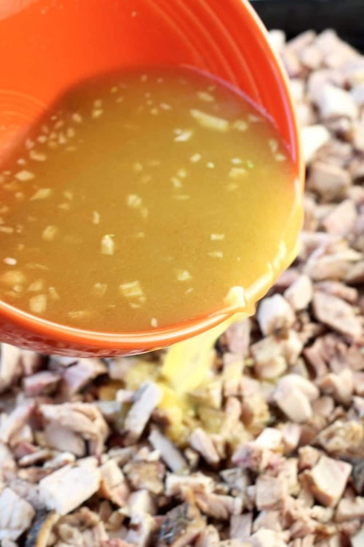 pouring citrus garlic sauce over chopped pork